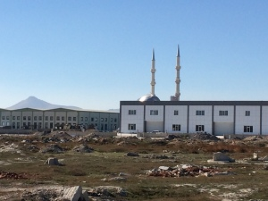 Typical scene riding into Konya--uncultivated land, industry and mosque